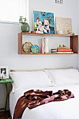 Double bed with white bed linen below floating shelf of books and pictures