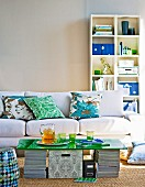DIY coffee table made from green glass sheet on stacked magazines in front of sofa and white shelving against wall