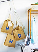 Blue letters on linen bags hanging next to clothes rack and iron on ironing board