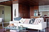 Many scatter cushions on modern sofa in front of open-plan fitted kitchen with dark wooden fronts and small breakfast bar