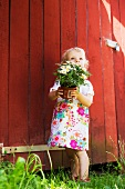 Little girl hold a potted plant in front of a shed