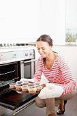 Frau hält Backblech mit verbrannten Cupcakes
