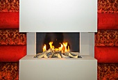 Minimalist gas fireplace in gray between red, velvet covered upholstered panels