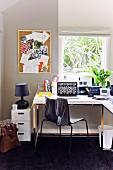 Ruhiger, heller Arbeitsraum in Gartenhäuschen mit Eckschreibtisch unter dem Fenster und schwarzem Teppichboden