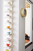 Coloured cups and saucers displayed on white shelves in window niche next to vintage submarine clock on wall