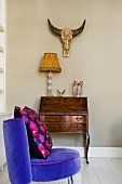 Purple velvet chair with retro-style cushion in front of Baroque bureau, table lamp and animal skull