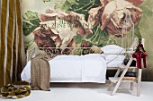 Ornate metal bed with white bed linen and vintage stepladder against wall with enormous rose motif