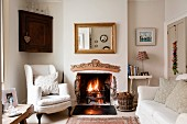 Traditional English living room with pale sofa set in front of open fireplace