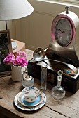 Demitasse with saucer and antique glass bottles in front of old mantel clock on wooden table