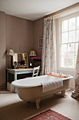 Free-standing vintage bathtub in front of window with floor-length curtains and dressing table with mirror in corner of room