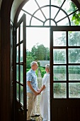 Älteres Paar von einer großen Fenstertür mit Rundbogen