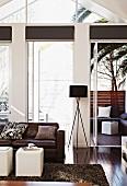 Wohnzimmer mit Ledersofa und gebeiztem Parkettboden; Terrasse mit Sitzgruppe unter Palmen