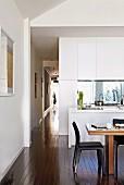 View from open-plan kitchen into narrow corridor with dark wooden floor