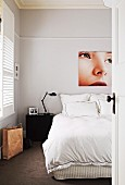 Large-format photo showing detail of woman's portrait above double bed with black bedside table and retro lamp