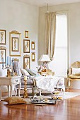Feminine, Baroque-style drawing room with glossy parquet floor and many gilt-framed pictures on wall; set silver tray, cake stand and champagne bucket on floor complete the French, aristocratic atmosphere
