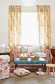Comfortable, romantic living room with floor-length floral curtains at bright window behind red and white striped sofa with many scatter cushions and light blue ottoman
