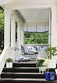 Summery wooden veranda with comfortable furniture and potted flowering plants