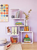 Modern shelving modules with rounded corners on wooden floor against lilac wall