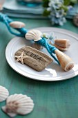 Rod decorated with felt ribbon and seashells on plate with name tag