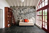 Minimalistisch eingerichtetes Wohnzimmer mit Natursteinwand