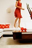 Frau im roten Kleid hüpft auf einem Sofa