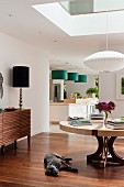 Open-plan interior with Japanese-style pendant lamp, elegant table lamp and green pendant lamps above kitchen counter