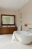 Spacious bathroom with spotlights in ceiling above oval bathtub, washstand area with exotic wood base cabinet and mirror with lamps on either side