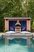 Rippled surface of pool in front of chic summer house with masonry barbeque against blue back wall