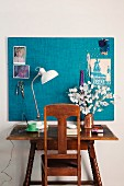 Dark wood, vintage desk and chair below pinboard with turquoise fabric cover