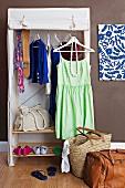 Faltbarer Kleiderschrank und Taschen auf dem Boden in einem Gästezimmer