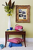 Vase of flowers on antique console table and photos in gilt frame on pastel-green wall