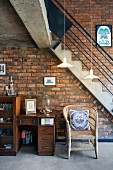 Vintage bureau, small cabinet and wicker chair in front of staircase against brick wall in loft-style interior