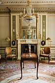 Table with bronze elements in front of fireplace with neoclassical, gilt stucco ornamentation; reflections of endless crystal chandeliers in two mirrors