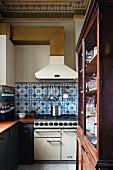 Blue and white wall tiles between gas cooker and extractor hood in old wooden kitchen with neoclassical stucco ceiling