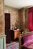 Chinese wall panels of painted rice paper, gilt bed frame and velvet throw embroidered with gold thread in stylish bedroom