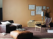 Modern living room in various shade of brown with floor cushion in front of huge leather armchair and framed wallpaper samples on wall