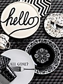 Various plates with black and white patterns and lettering on tablecloth with three-dimensional pattern