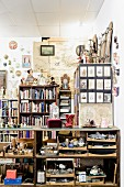 Half-height shelves full of objets d'art and bookcases against wall in cluttered room