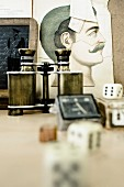 Vintage binoculars and dice on table in front of old drawing