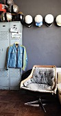 Vintage swivel chair in front of motorbike jacket hanging on locker and collection of helmets on grey wall