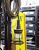 Vintage lamp with coiled cable and yellow, sheet metal advertising panel in front of chest of drawers