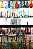 Collection of coloured glass bottles and vases on glass partition shelving