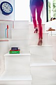 Woman walking up modern samba staircase made from white-painted wood