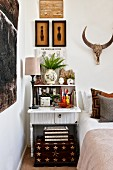 Open bureau with table lamp next to bed and hunting trophy on wall