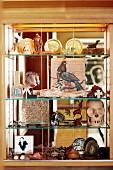 Nick-nacks on glass shelves built into niche