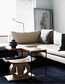Antique stool with curved seat and side table in front of corner sofa in living room