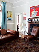 Brown leather sofa and armchair in front of fireplace in corner of traditional living room