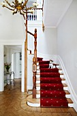 Traditional, white stairwell with red runner on winding staircase