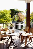 Classic, wooden chairs and traditional side table on wooden floor of colonial-style veranda