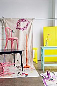 Freshly-painted wooden furniture in pink, mint-green and dark blue in front of draped dust sheets; table top and trestle painted neon yellow in background